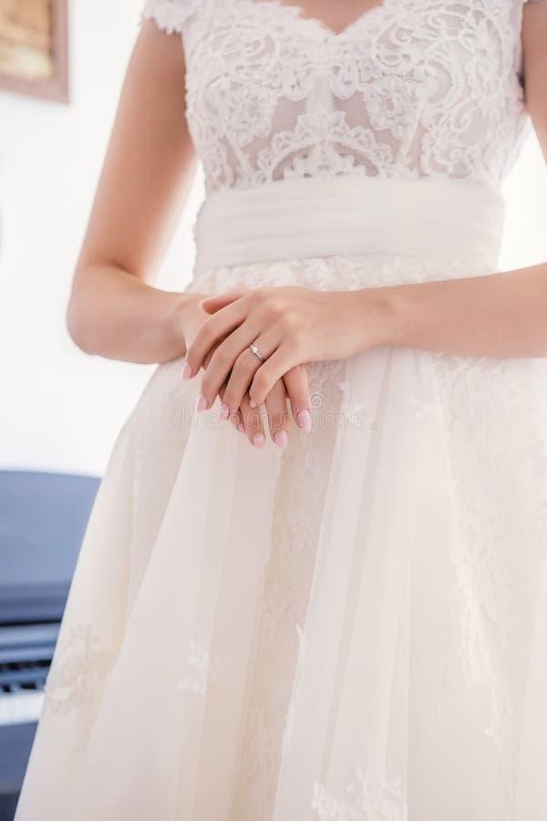 Рука Bride's с обручальным кольцом на платье стоковое фото rf