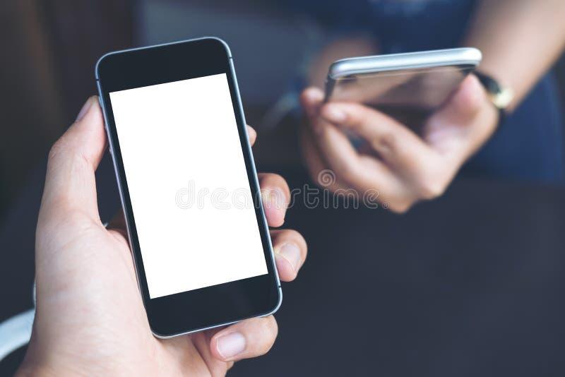 Рука ` s бизнесмена держа черный мобильный телефон с пустым белым экраном с предпосылкой коммерсантки стоковое фото rf