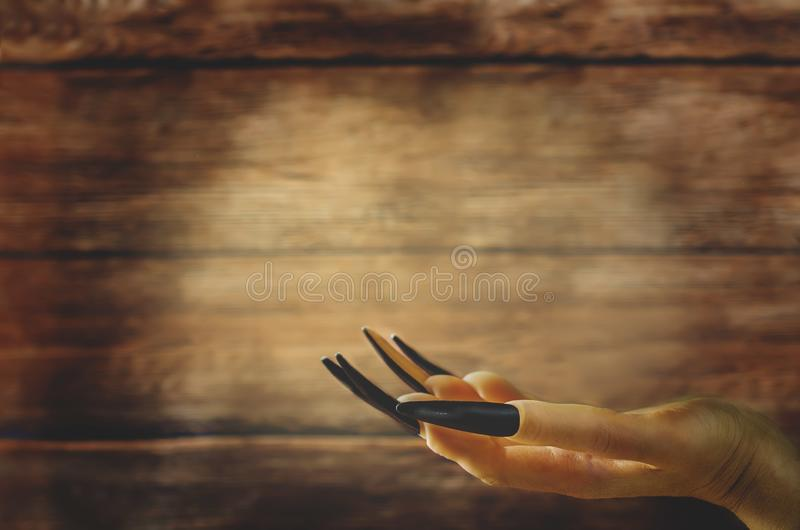 Рука ` s ведьмы на темной деревянной предпосылке на хеллоуин стоковые изображения rf