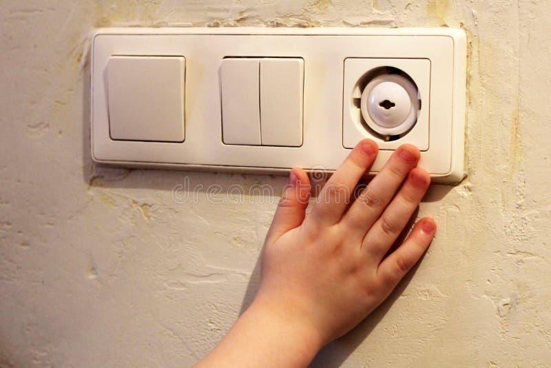 Рука ` s детей символизируя опасность электрического тока стоковое фото