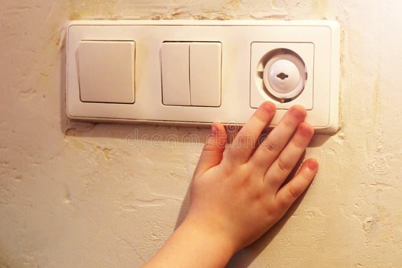 Рука ` s детей символизируя опасность электрического тока стоковое изображение