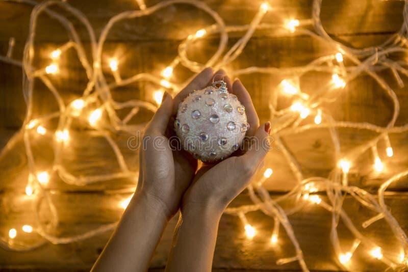Рука ` s женщины держа орнамент рождества сняла na górze деревянной предпосылки стоковые изображения rf