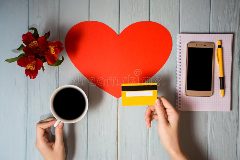 Рука ` s женщины держит кредитную карточку над таблицей, онлайн подарками покупок стоковая фотография rf