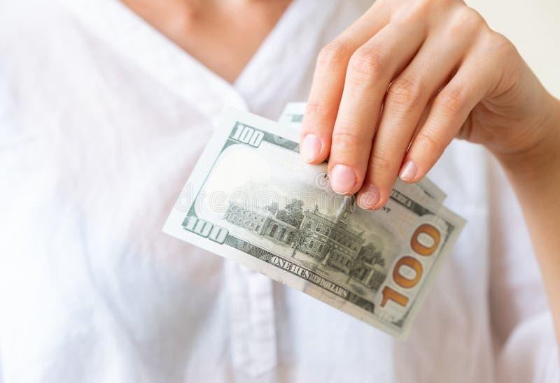 Рука ` s женщины держит 2 сотни долларов стоковые изображения rf