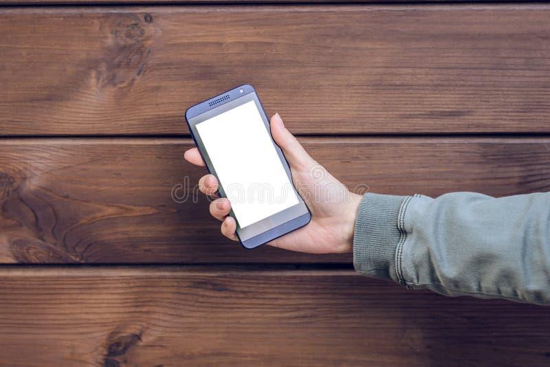 Рука ` s женщины показывая пустой пустой сенсорный экран на ее мобильном телефоне против коричневого деревянного телефона mobil м стоковое изображение rf