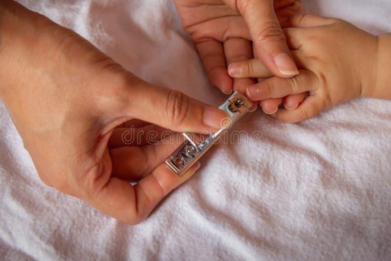 Рука ` s матери использует ножницы ногтя для того чтобы отрезать ноготь к младенцу стоковые фотографии rf