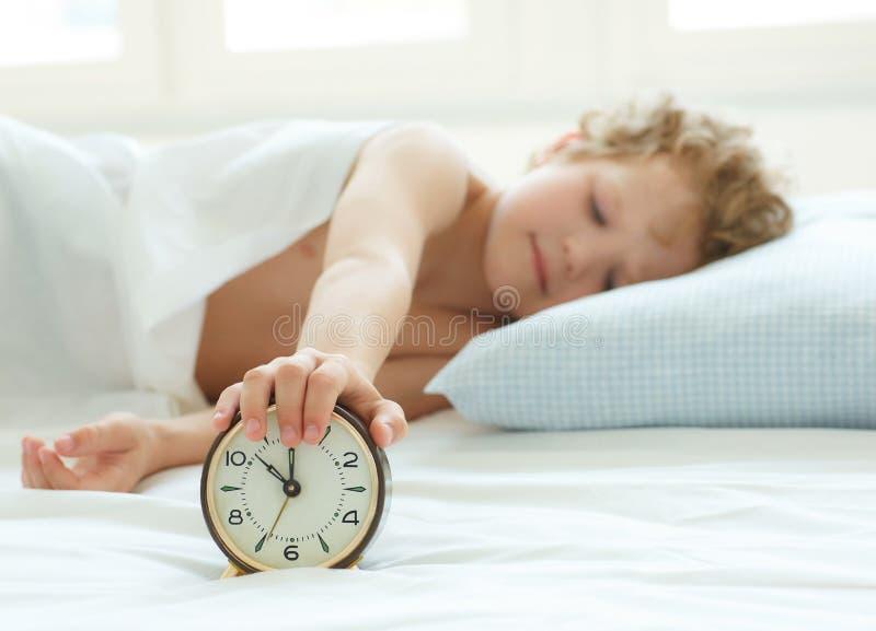 Рука ` s мальчика достигая для будильника для того чтобы повернуть его  стоковая фотография