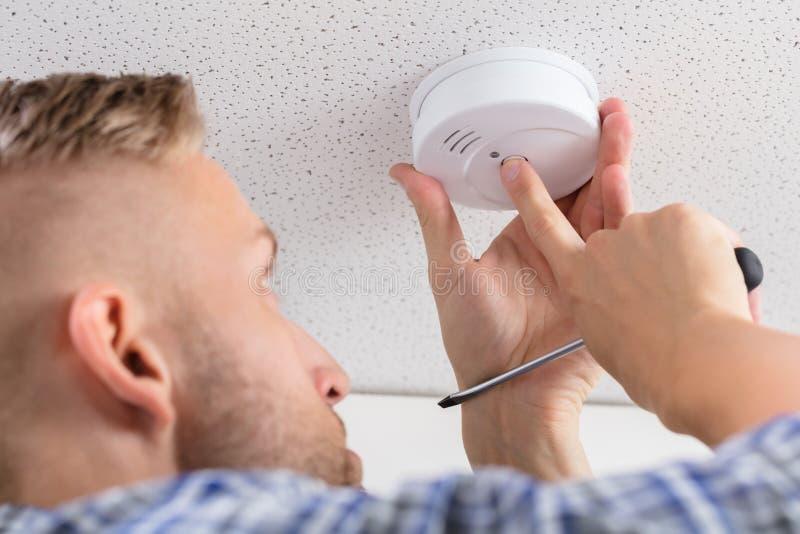 Рука ` s персоны устанавливая индикатор дыма на потолок стоковые фото