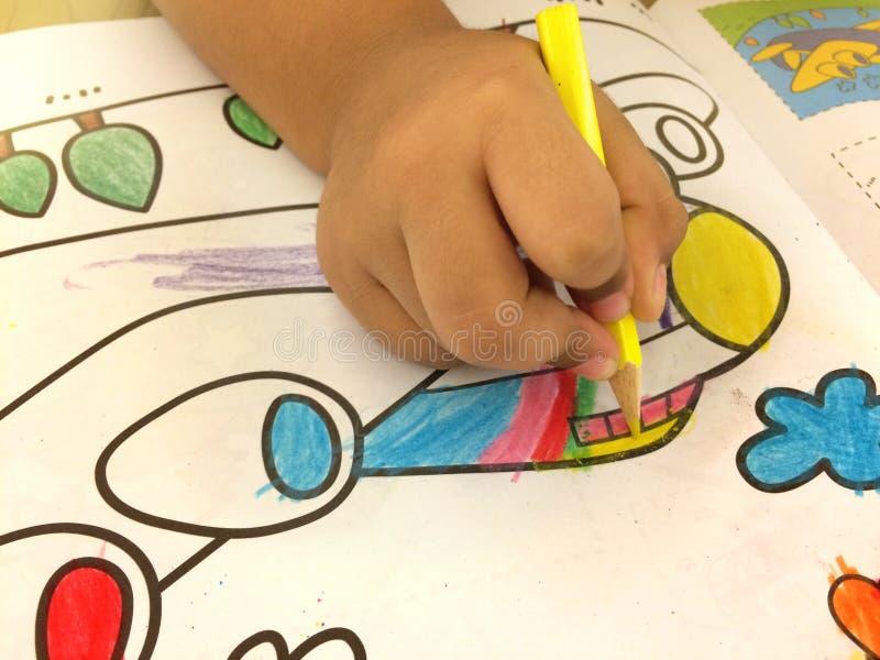 Рука ` s ребенка красит на бумаге Самолет и имеет f стоковые изображения rf