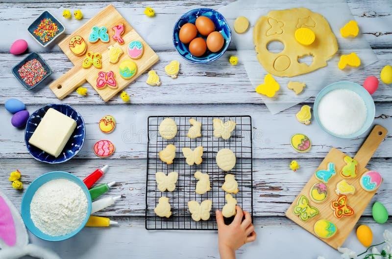 Рука ` s ребенка с печеньями и ингридиентами пасхи сахара для bakin стоковые фотографии rf