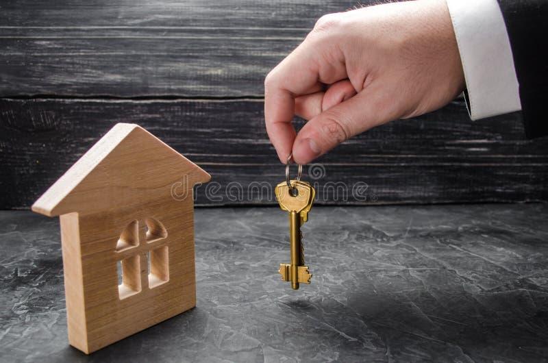 Рука ` s риэлтора держит ключи к дому Деревянный дом Концепция покупать и продавать квартиры стоковые изображения rf