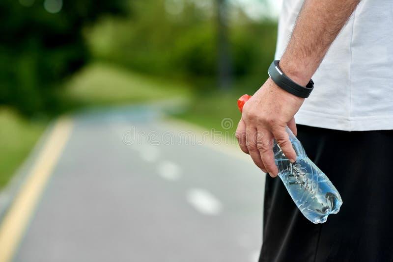 Рука ` s спортсмена держа беговую дорожку runningon бутылки с водой стоковые фотографии rf