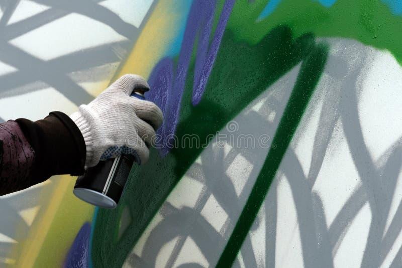 Рука ` s художника с воздушным шаром краски рисует граффити на белой стене стоковая фотография