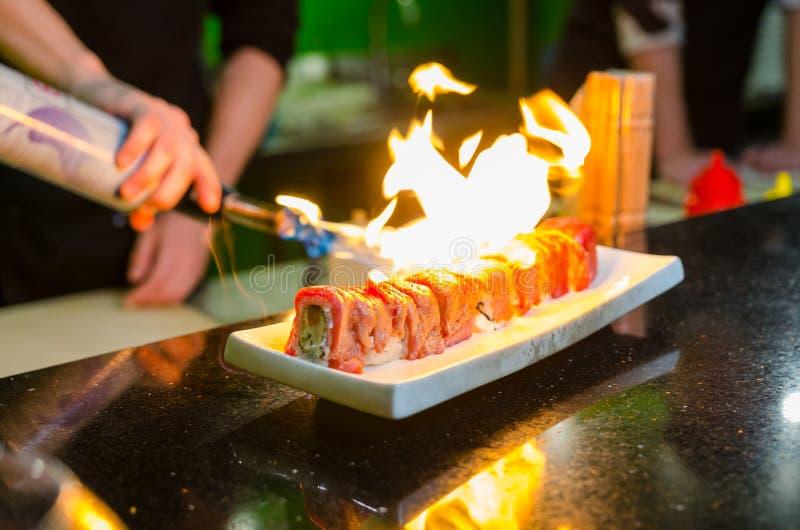 Рука ` s человека держа горелку факела Шеф-повар подготавливает суши стоковая фотография rf