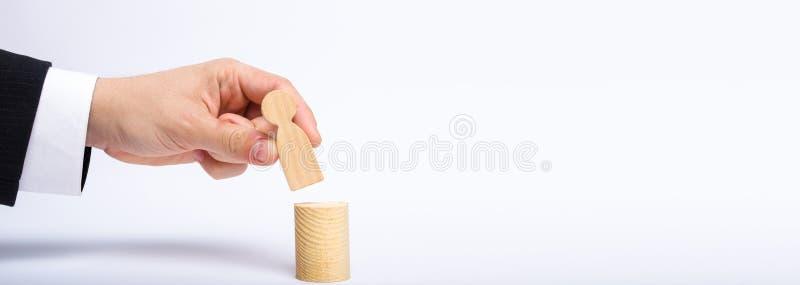 Рука ` s человека кладет персону диаграмма ` s na górze его нового бизнесмена столба a назначает персону к распорядительскому пол стоковое фото rf