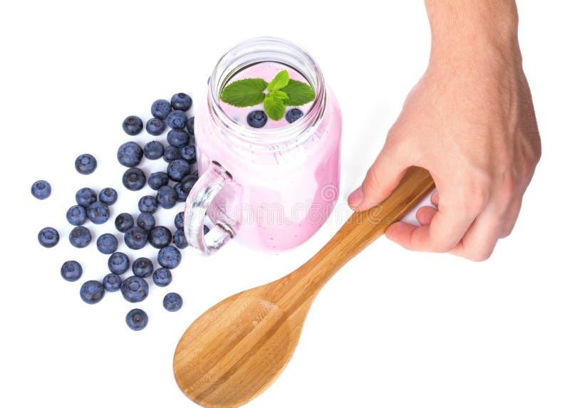 Рука ` s человека держа ложку Продукты ягоды изолированные на белой предпосылке Естественный milkshake голубики в опарнике каменщ стоковое изображение