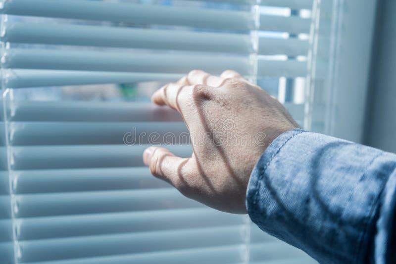 Рука ` s человека раскрывает шторки или jalousie в солнечном дне стоковое изображение