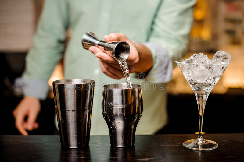 Руки бармена лить питье в джиггер для того чтобы подготовить конец коктеиля вверх стоковая фотография