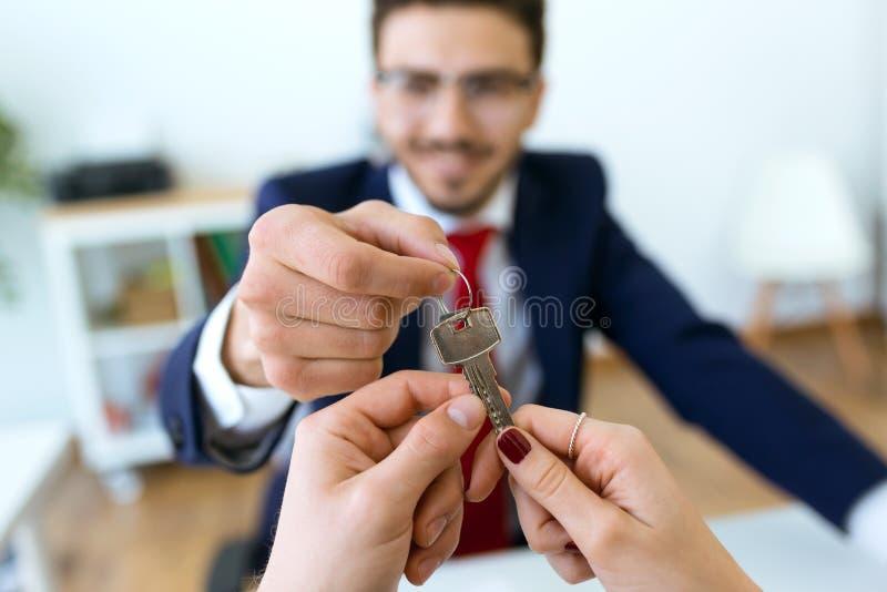 Руки бизнесмена над ключами дома к паре после закрывать продажу стоковая фотография rf