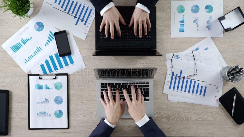 Руки бизнесменов печатая на компьтер-книжках напротив одина другого, смешного взгляд сверху стоковое фото