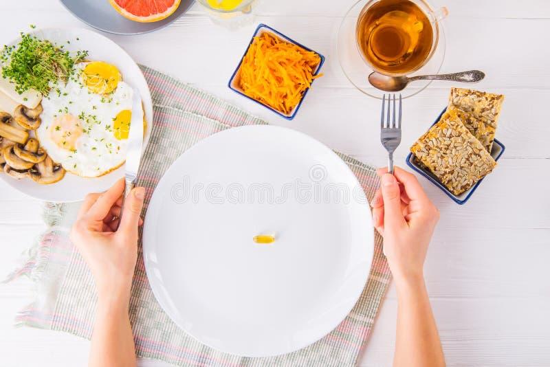 Руки взгляд сверху женские держа нож и плиту вилки и белых с пилюлькой витамина на, который служат деревянном столе с едой завтра стоковая фотография rf
