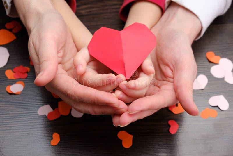 Руки взрослого и ребенка держа сердце формируют, здравоохранение, концепция дарят и страхования семьи стоковое изображение