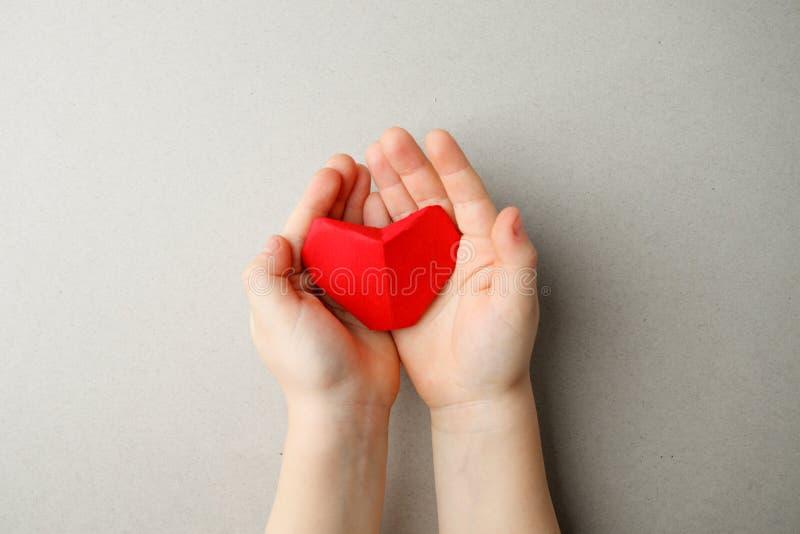 Руки взрослого и childs держа красное сердце бумаги origami в руках на сером космосе экземпляра предпосылки, плоском положении кр стоковое фото