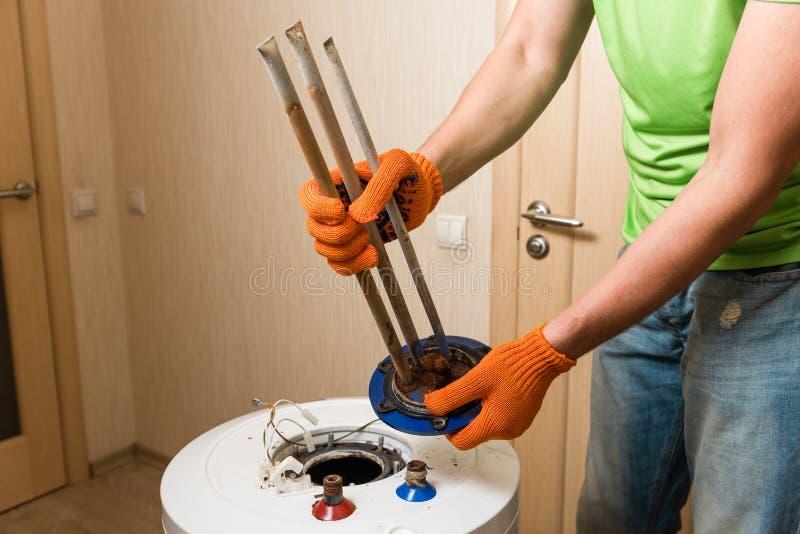 Руки водопроводчика держат старый ржавый элемент жары стоковые фотографии rf