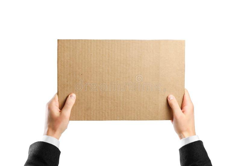 Руки в белой рубашке и черной куртке держа часть картона белизна изолированная предпосылкой Подготовленный для вашего текста стоковое изображение