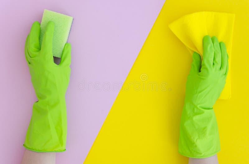 2 руки в зеленых перчатках держат губку на предпосылке цвета желтого пинка яркой разделенной Плоское положенное duotone космоса э стоковые фото