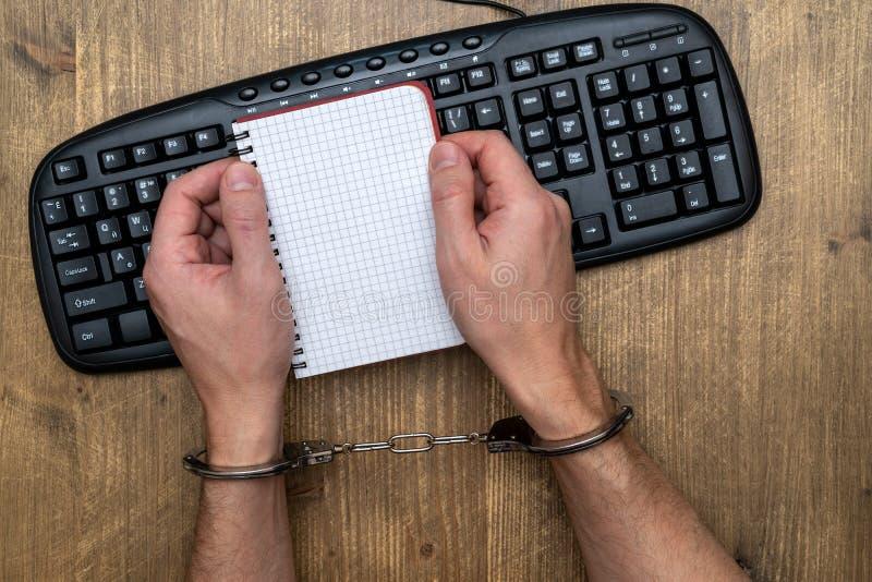 Руки в наручниках над клавиатурой компьютера стоковые изображения rf