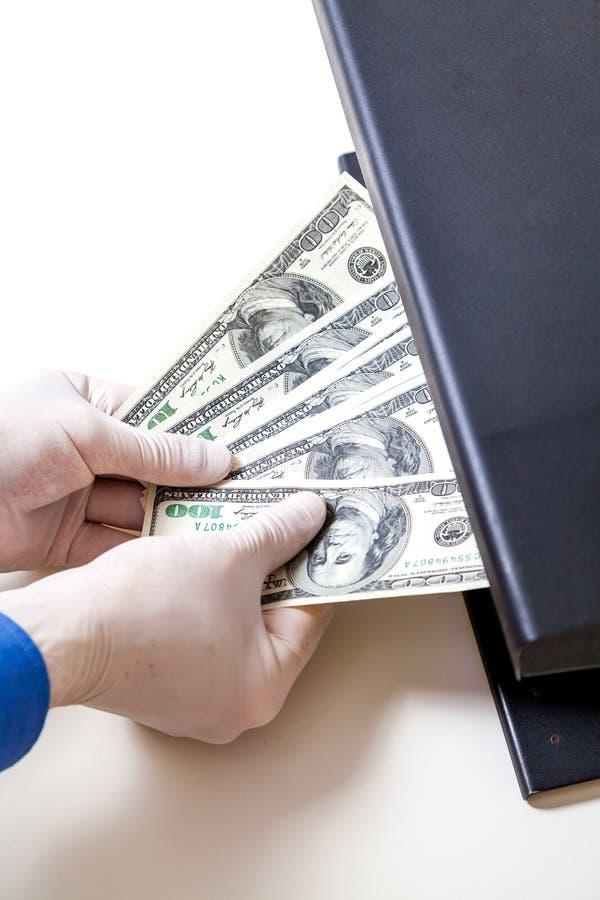Руки в перчатках держат вентилятор долларов в переднем детекторе стоковое фото