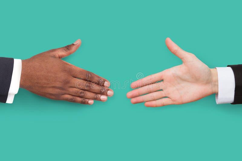 Руки готовые для рукопожатия на предпосылке бирюзы стоковое фото
