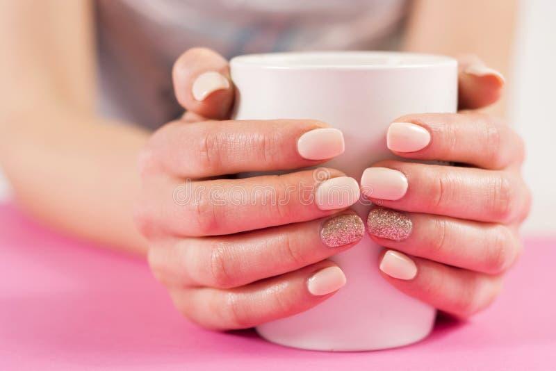 Руки девушки с напихивают ногтей маникюра держа чашку кофе на розовом столе стоковые фотографии rf