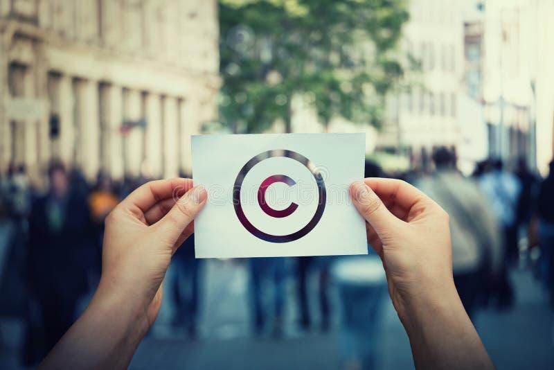 Руки держат бумагу с символом авторского права Международный знак интеллектуальной собственности законных прав, патентная защита  стоковые изображения rf