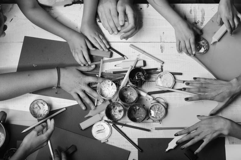 Руки держат красочные отметки, карандаши и краски Поставки искусства в больших и крошечных руках на белой предпосылке стоковое изображение