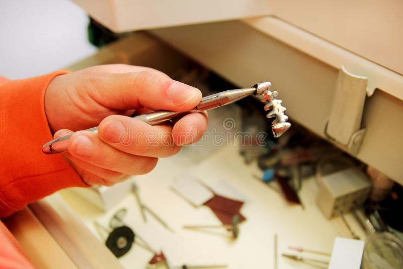 Руки держат крону стального металла зубоврачебную стоковая фотография rf