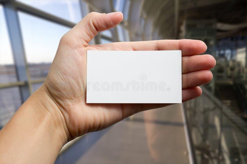 Руки держа белую карточку id делового визита, подарок, билет, пропуск, присутствующий конец показа вверх на запачканной голубой п стоковые изображения
