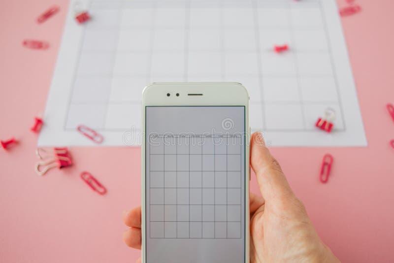 Руки держа белый смартфон на предпосылке календаря бумаги Яркие розовые зажимы и штыри разбросаны вокруг стоковая фотография