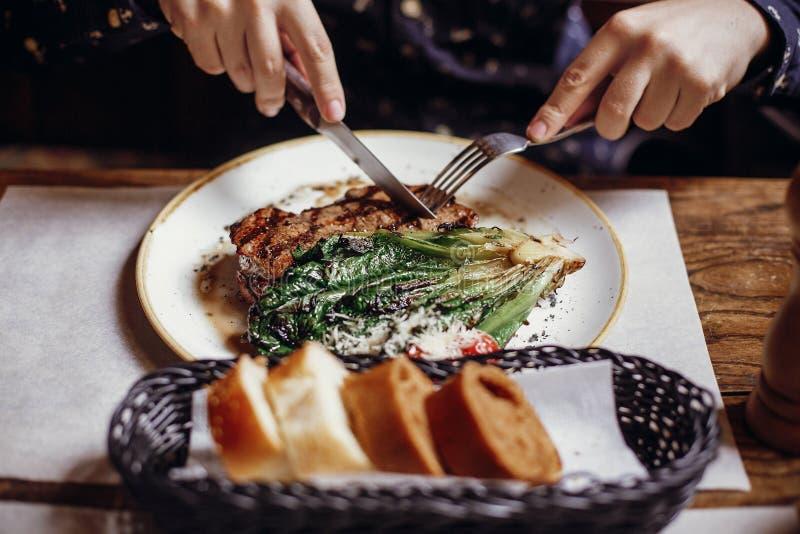 Руки держа вилку и нож и есть очень вкусные сочные wi стейка стоковая фотография rf