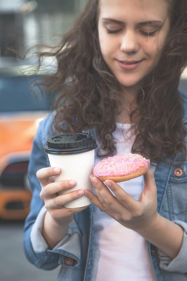 Руки держа донут и кофе на предпосылке занятой метрополии стоковые фотографии rf