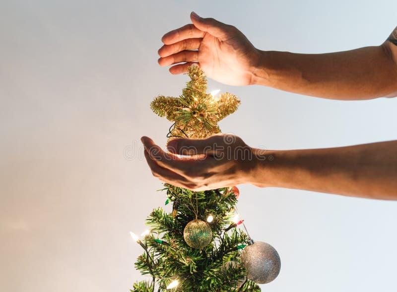 Руки держа золотую звезду на рождественской елке с яркими светами, концепции праздника рождества стоковая фотография rf