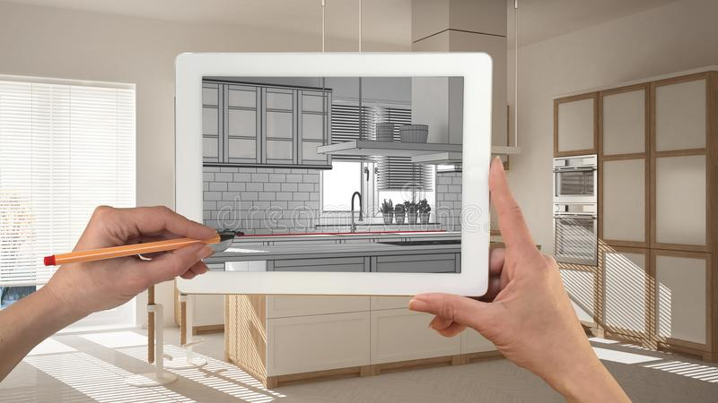 Руки держа и рисуя на таблетке показывая современный эскиз кухни Реальная законченная минималистская белая и деревянная кухня в b иллюстрация штока