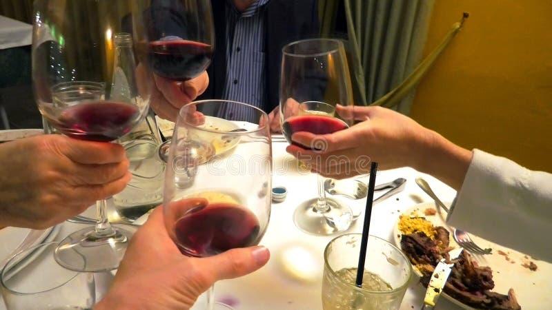 4 руки держа красное вино и приветственные восклицания стоковая фотография rf