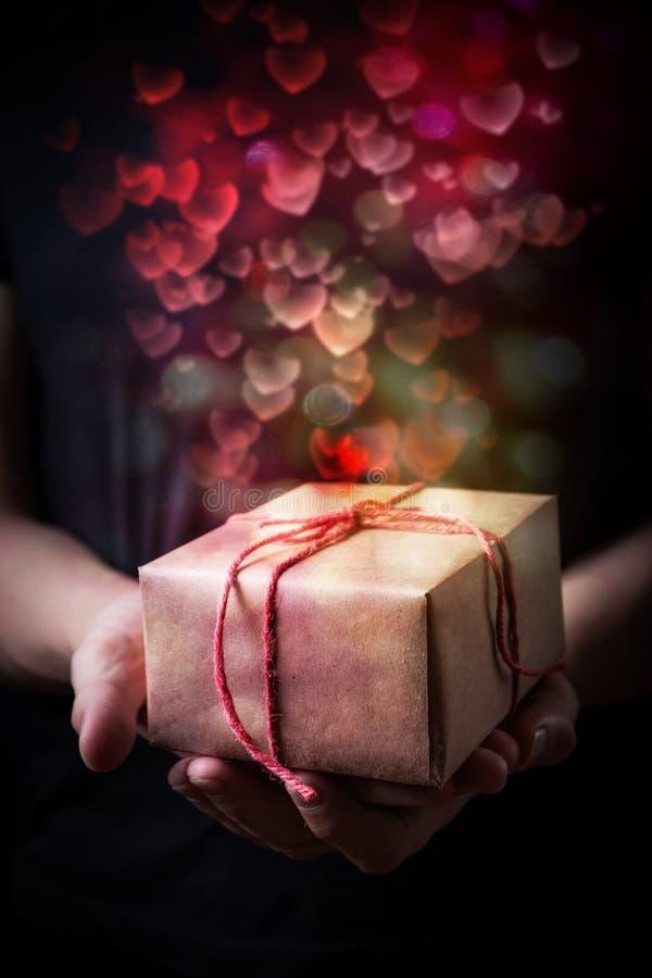Руки держа малый подарок стоковые изображения rf