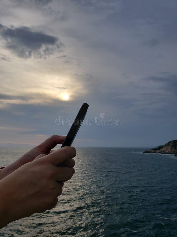 руки держа смартфон и предпосылку с тропическим ландшафтом стоковые фотографии rf