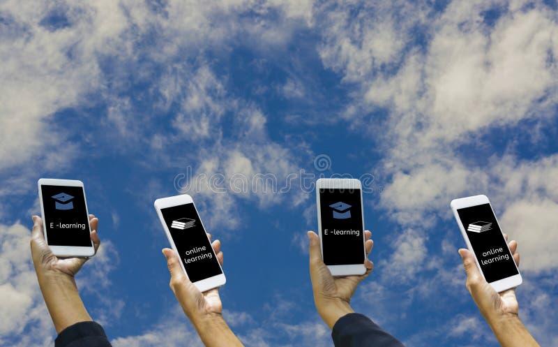 Руки держа смартфон онлайн и обучение по Интернету, со значком книги и шляпы, предпосылкой голубой, свободой концепции онлайн и стоковые изображения