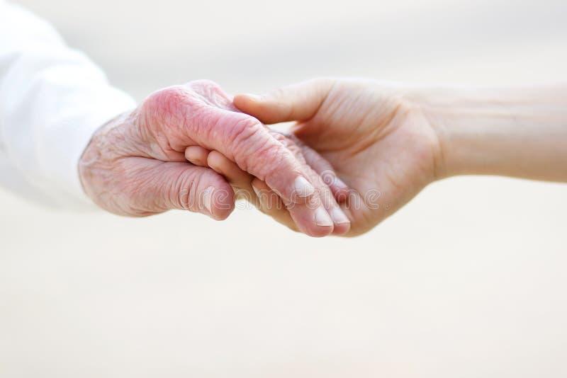 руки держа старших женщин молодым стоковая фотография