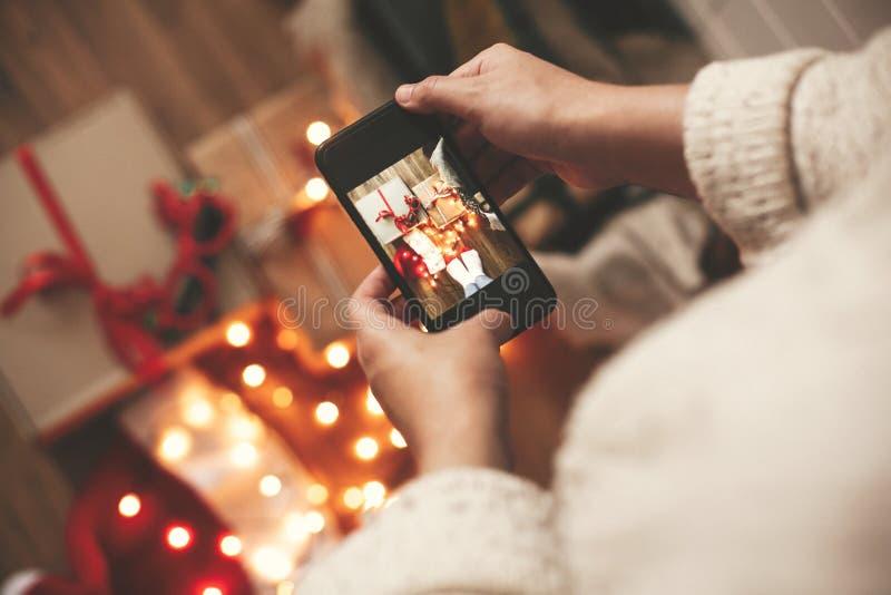 Руки держа телефон и принимая фото подарочных коробок рождества, шляпу santa, света на деревянной предпосылке в темной комнате Ст стоковые изображения rf