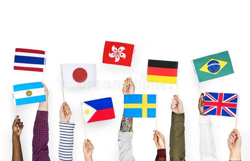 Руки держа флаги international изолированный на белой предпосылке стоковое изображение